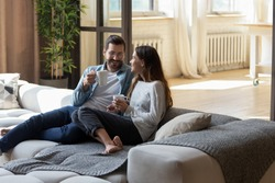Loving couple relaxing on cozy sofa in living room, drinking hot beverages, tea or coffee, happy smiling man and woman holding white cups sitting on couch, chatting, talking, spending lazy weekend