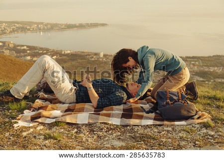 Loving couple resting on peak of mountain above the bay in summer
