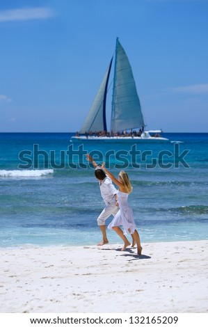 Loving couple runs on a tropical beach. Jump. Dominican - stock photo