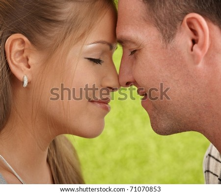 Loving couple's faces in closeup, foreheads touched, facing each other, smiling.?