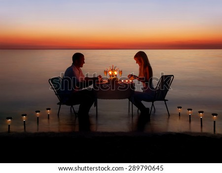 Loving couple share a romantic dinner with candles and lanterns light way at sea beach in water against wonderful sunset #289790645