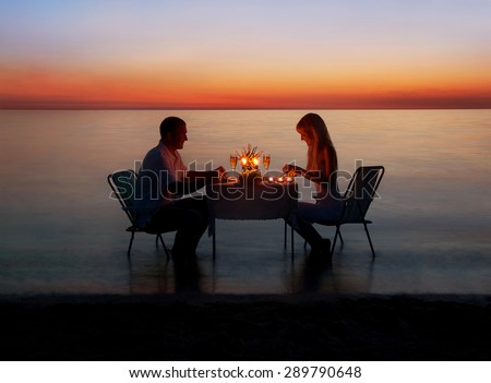 Loving couple share a romantic dinner with candles at sea beach in water against wonderful sunset