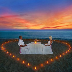 Loving couple share romantic dinner with candles heart at sea beach sand looking for wonderful sunset