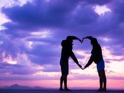 Loving couple showing heart symbol on hands,twilight background