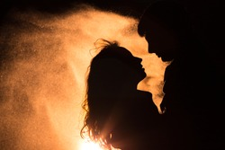 Loving couple silhouette. The wind carries sand.