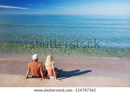 loving couple sitting on the sea sand beach and look at the blue sky - stock photo