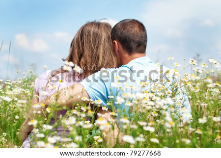 loving couple sitting together in the middle of flowers