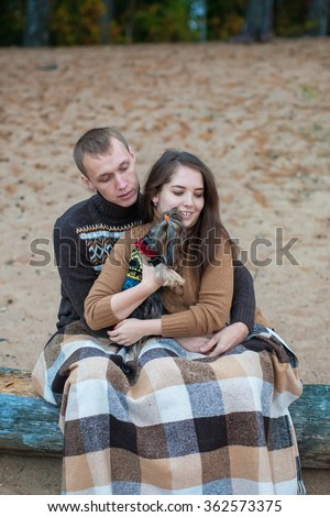 Loving couple sitting with a dog on a log on the rocky beach