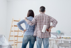 Loving couple staring at their freshly painted room, back view: home renovation and relationships concept