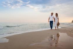 Loving couple walks along the sandy seashore at sunset