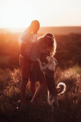 loving couple with a dog on the background of beautiful orange sunset