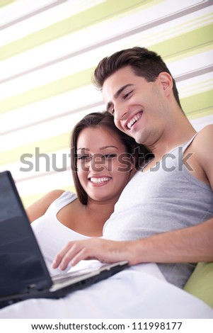 Loving couple with laptop and lying in bed