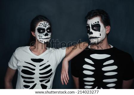 Loving couple with skull face art in costume of skeletons on dark background, Halloween theme