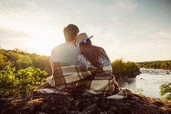 Loving couple wrapped in plaid blanket, sitting on mountain outdoors. Rear view. Man and woman travel together. Romantic traveler couple watching beautiful landscape, enjoying nature on sunset.
