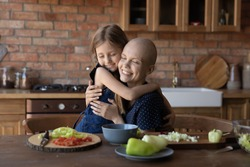 Loving cute little girl child hug sick cancer patient bald mother cooking healthy food salad in kitchen together, caring small daughter embrace show love support to ill mom, feel grateful thankful
