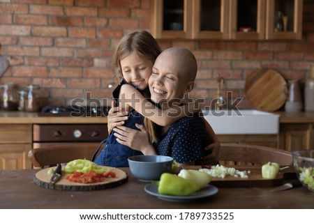 Loving cute little girl child hug sick cancer patient bald mother cooking healthy food salad in kitchen together, caring small daughter embrace show love support to ill mom, feel grateful thankful Foto d'archivio ©
