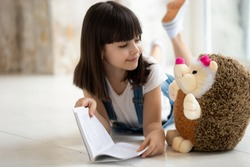 Loving cute little girl lying on warm home floor reading interesting story to toy hedgehog friend, happy small preschooler kid have fun playing learning with stuffed animal, enjoy fairy tale in book