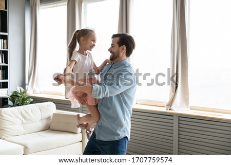 Loving dad holds on hands small daughter she wears crown imagines herself like princess, people dancing in living room, enjoy holiday life event birthday party. Happy fatherhood, family bonds concept