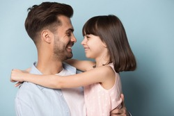 Loving daddy look at little adorable daughter feeling love isolated on blue studio background profile faces side view, deep devotion warm relationships, love care, closest person, fathers day concept