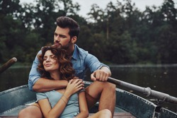 Loving everything about her. Beautiful young couple embracing and looking away while enjoying romantic date on the lake