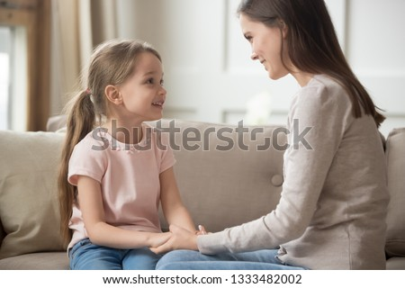 Loving family happy mother and cute child girl holding hands talking sitting on sofa at home, caring elder sister mom baby sitter having friendly trust conversation with preschool little kid daughter