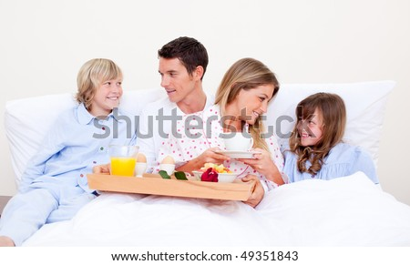 Loving family having breakfast sitting on bed at home