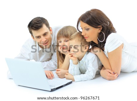 Loving family looking at a laptop lying down on bed at home