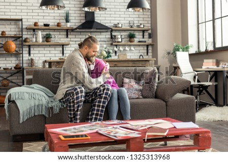 Loving father. Loving father hugging his lovely daughter while sitting in living room together #1325313968