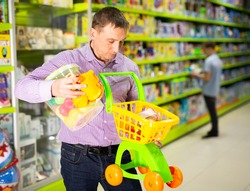 Loving father visiting modern toy store in search of new playthings for his child