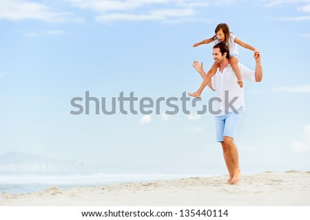 loving father with daughter on shoulders walking on the beach carefree and happy