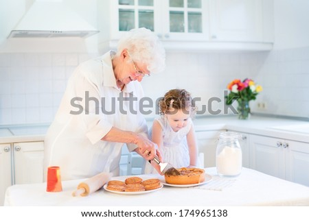 Loving grandmother baking an apple pie with her adorable toddler granddaughter in a beautiful white kitchen