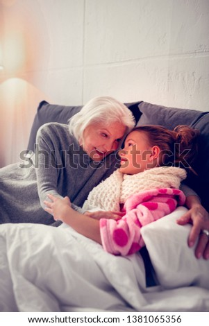 Loving granny. Caring loving granny hugging her cute girl staying in bed feeling sick after catching cold