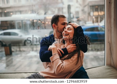 Loving guy hugs his beautiful happy girlfriend sitting on the windowsill in a cozy cafe. #1296683959