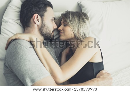 Loving happy couple in love smile and hug each other on the bed, in big bedroom, Love story concept #1378599998
