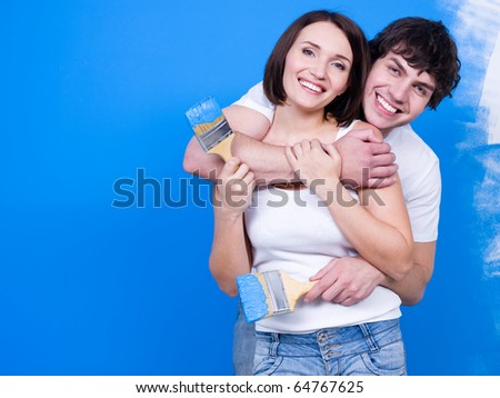 Loving happy couple standing in embrace with paintbrush near the wall