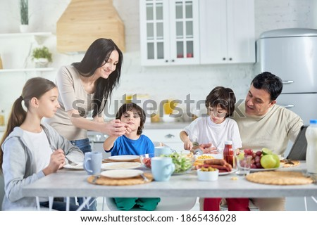 Loving hispanic parents taking care of their little children, entertaining them while having lunch together at home Foto stock ©