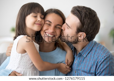 Loving husband and cute kid daughter embracing kissing happy mom wife on cheek congratulating with mothers day, little child girl and dad hugging smiling mum, caring family of three bonding together