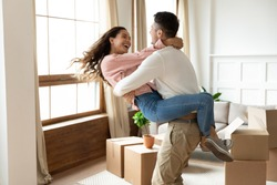 Loving husband lifting excited wife, celebrating moving day, having fun in modern living room with cardboard boxes with belongings, happy young couple purchasing new house, mortgage and relocation