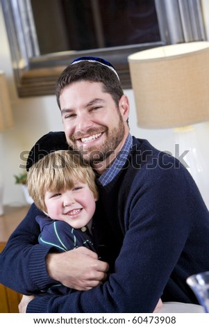 Loving Jewish father and young 4 year old son wearing yarmulkes