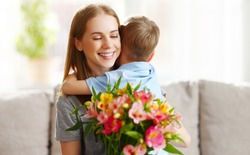 Loving little son hugging happy mom and greeting with bouquet of Alstroemerias during Mothers day celebration at home