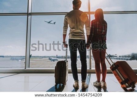 Loving man and woman are standing near window at airport. They are holding each other hand and looking outside at planes while looking forward to their flight. Copy space in left side
