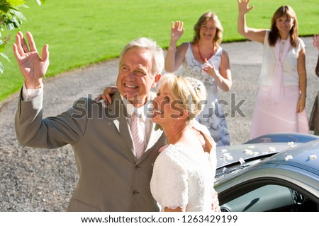 Loving mature bride and groom outdoors waving at guests on wedding day