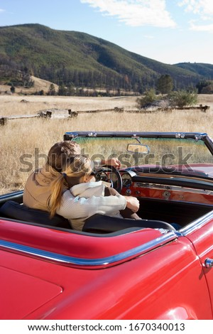 Loving mature couple driving classic red convertible car on road trip