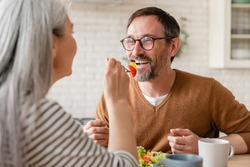Loving mature wife feeding middle-aged caucasian husband with vegetable salad during breakfast at home. Love and relationship concept. Family couple eating vegetarian food