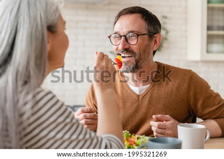 Loving mature wife feeding middle-aged caucasian husband with vegetable salad during breakfast at home. Love and relationship concept. Family couple eating vegetarian food Foto stock ©