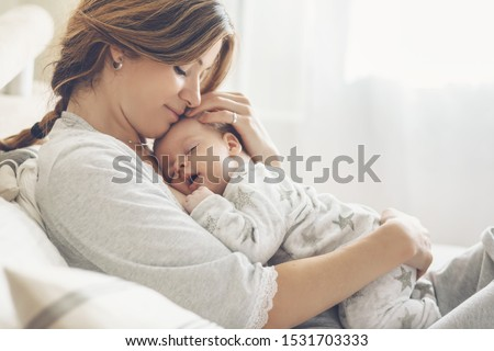 Photo of  Loving mom carying of her newborn baby at home. Bright portrait of happy mum holding sleeping infant child on hands. Mother hugging her little 2 months old son.