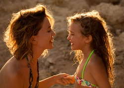 Loving moments of mother and child. Mom and girl on sunset