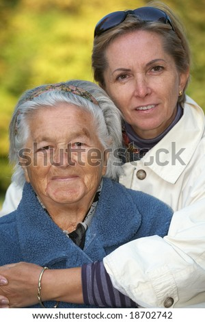 Loving mother and daughter in the park. Focus on the elderly woman;