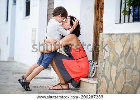 Loving mother and son hugging outdoors on beautiful summer day - stock photo