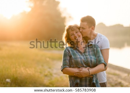 Shutterstock Loving mother being kissed by her adult son as he hugs her from behind